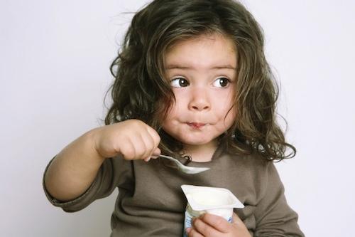 Девочка кушает йогурт