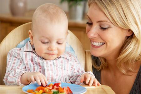 Ребенок за столом и тарелка фруктов