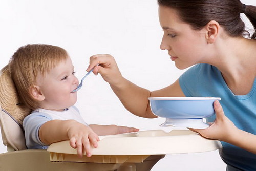 мама кормит ребенка с ложки